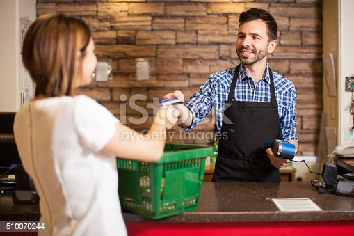 istock Cashier receiving a credit card payment 510070244
