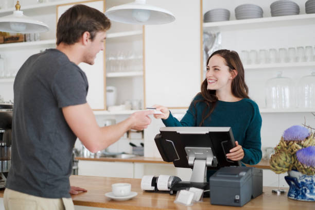Cashier receiving payment from customer in cafe Happy female cashier receiving credit card from male customer in coffee shop. Smiling young woman is receiving payment in cafe. They are wearing casual. retail equipment stock pictures, royalty-free photos & images