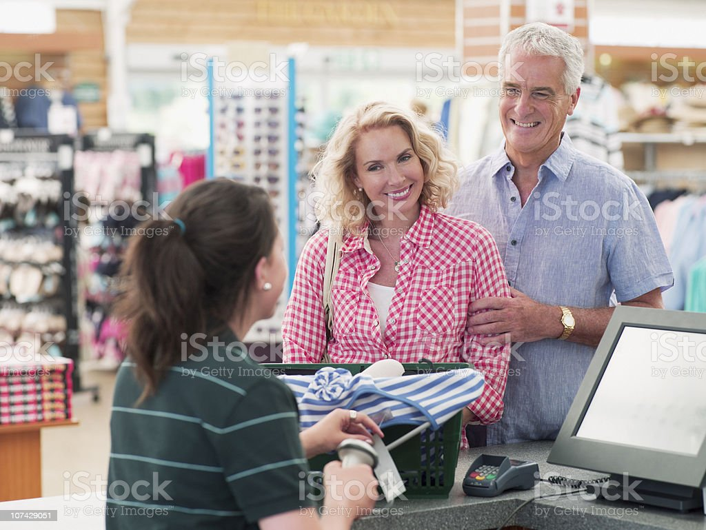 Cashier scanning couples purchases in store royalty-free stock photo