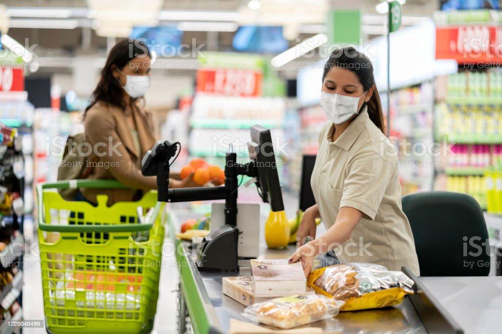 Kassier die producten bij een kruidenierswinkel scant die een facemask draagt - Royalty-free Alleen volwassenen Stockfoto