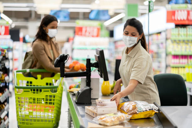 cashier scanning products at a grocery store wearing a facemask - servizi essenziali foto e immagini stock