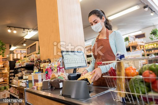 Latin American cashier working at the supermarket wearing a facemask while scanning products – quarantine lifestyle concepts