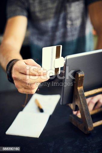 178974134istockphoto Cashier's hand swiping card digital tablet 588390160
