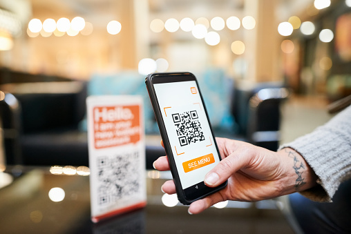 Close-up of hand of a woman scanning the qr code with her phone to make a cashless payment in a cafe