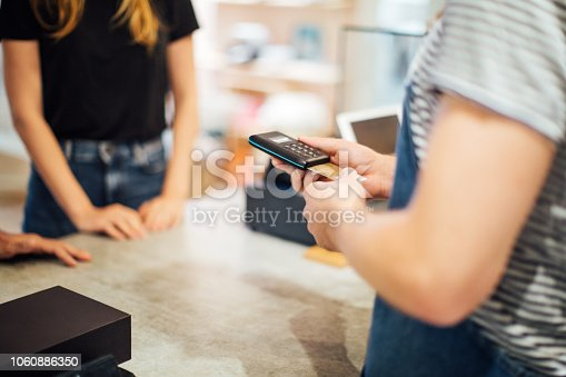 Cashiers hand inserting credit card in a terminal machine for payment at cafe. Cashless payment for coffee at a cafe.