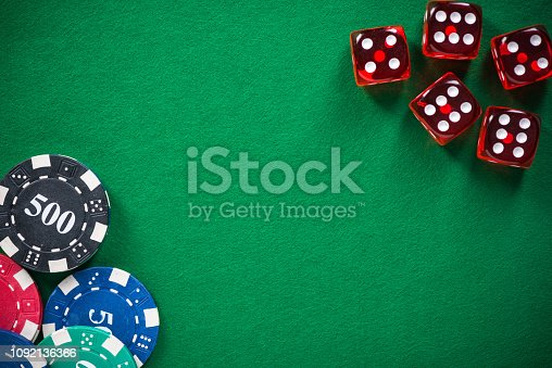 Casino chips and red dices on green empty felt.