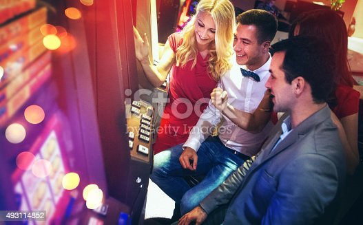 Group of early 30's people having fun in a casino by playing slots. There are two men and two women playing on one machine. Side view, high angle shot. Slots are lit red and purple.