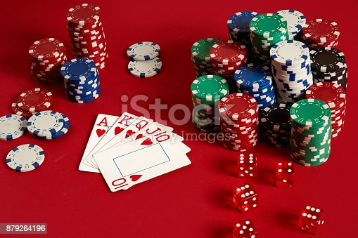 Casino gambling poker equipment and entertainment concept - close up of playing cards and chips at red background. Royal flush heart. Casino background. Copy space. Still life