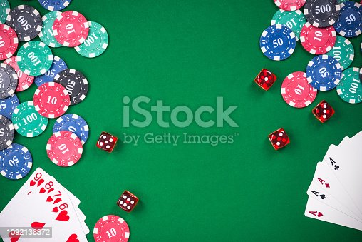 Casino games related items on green table, copy space.
