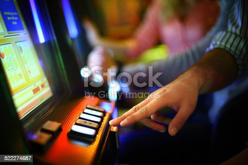 Closeup of unrecognizable caucasian man making money on  slot machine in casino. He's playing slot poker. There are blurry people in background also playing.