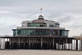 Casino on pier of Blanckenberge at North Sea in Belgium. Some people are on pier. Sky is overcast, end of winter season