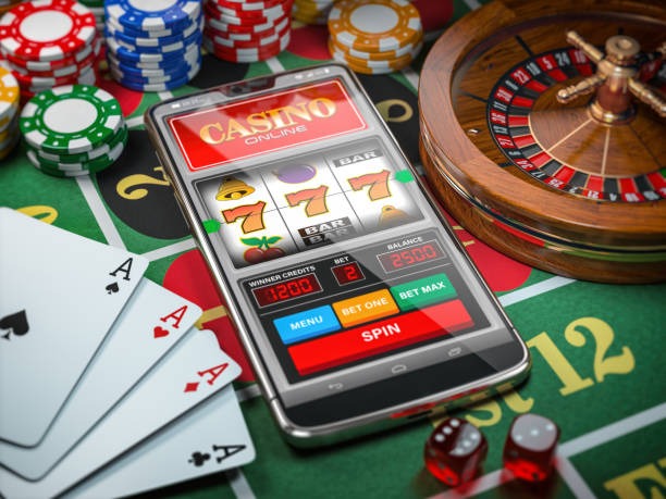 Casino online. Smartphone or mobile phone, slot machine, dice, cards and roulette on a green table in casino. stock photo