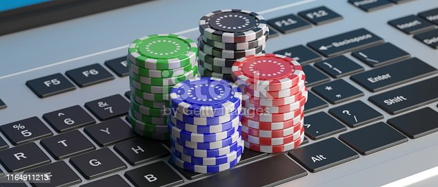 istock Casino poker chips stacks on a laptop keyboard. 3d illustration 1164911213