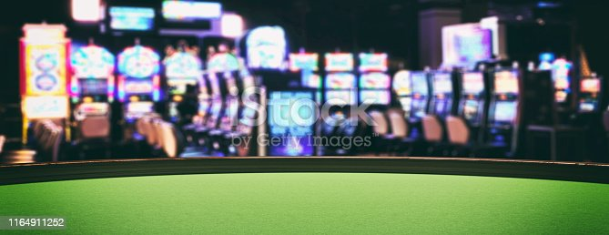 istock Casino slot machines, green felt roulette table closeup view. 3d illustration 1164911252