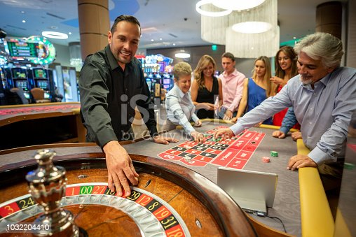 Casino worker ready to release the ball on the roulette wheel while others are still placing bets on table smiling