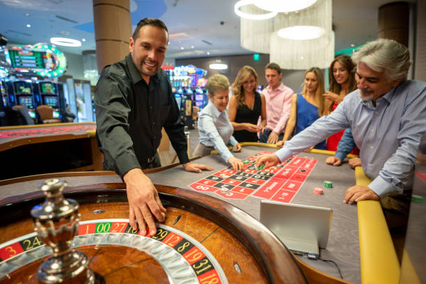 Casino worker ready to release the ball on the roulette wheel while others are still placing bets on table Casino worker ready to release the ball on the roulette wheel while others are still placing bets on table smiling game of chance stock pictures, royalty-free photos & images