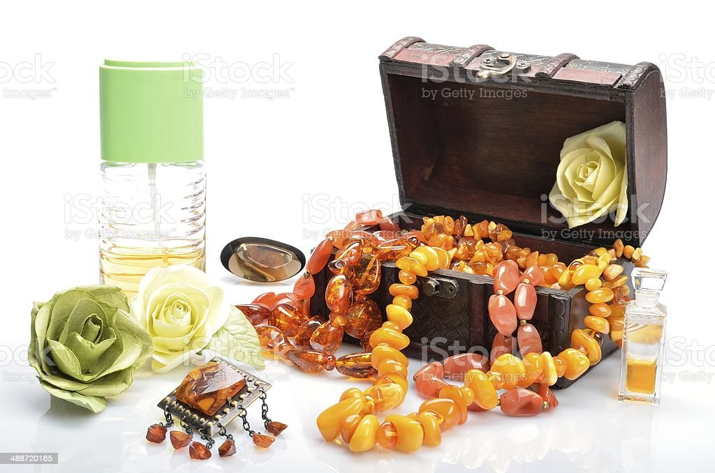 Casket with women's jewelry, succinic brooch, perfume and flowers royalty-free stock photo