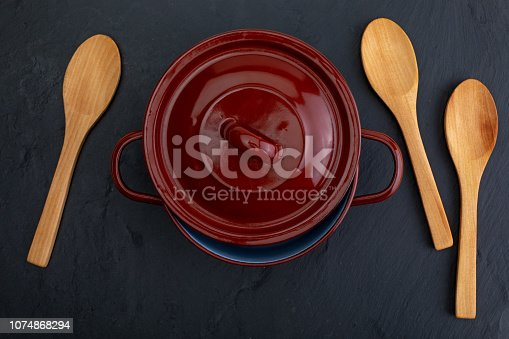 istock Casserole and wooden spoons on black slate background with texture. Space to insert your text here. Letter for restaurants. (Food concept of spoon, pot). 1074868294