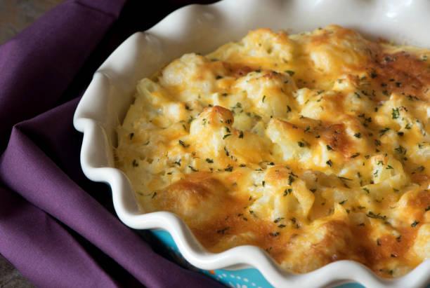 kasserolle kohl ist mit käse bestreut und gebacken - käse zucchini backen stock-fotos und bilder