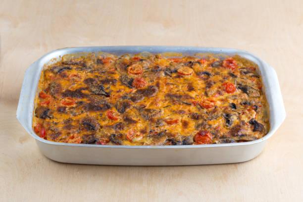 auflauf auf einem backblech auf einem holztisch. das fertige gericht wird im ofen gebacken. - huhn brokkoli auflauf stock-fotos und bilder
