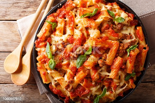 Casserole ziti pasta with minced meat, tomatoes, herbs and cheese close-up on a plate. Horizontal top view from above