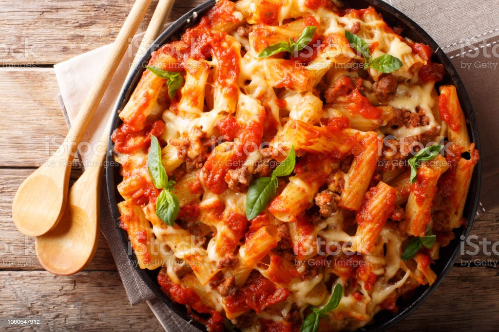 Casserole ziti pasta with minced meat, tomatoes, herbs and cheese close-up. Horizontal top view stock photo