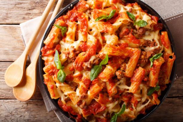 braadpan ziti pasta met gehakt vlees, kaas, tomaten en kruiden close-up. horizontale bovenaanzicht - gebakken in de oven stockfoto's en -beelden