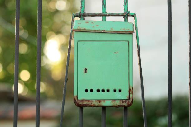 grüne kiste auf tor - briefhalter stock-fotos und bilder