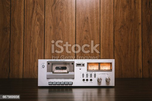 A vintage looking tape player / recorder stereo sits on the counter of a 1970's - 1980's  living room with wood paneling.   Horizontal image with copy space.