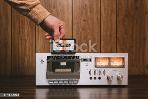 A vintage looking tape player / recorder stereo sits on the counter of a 1970's - 1980's  living room with wood paneling.  A mans hand reaches down to insert a cassette into the machine.  Horizontal image with copy space.
