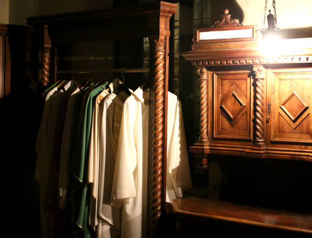 cassock for priests in the sacristy of an ancient Christian chur Many cassock for dressing priests in the sacristy of an ancient Christian church clergy stock pictures, royalty-free photos & images