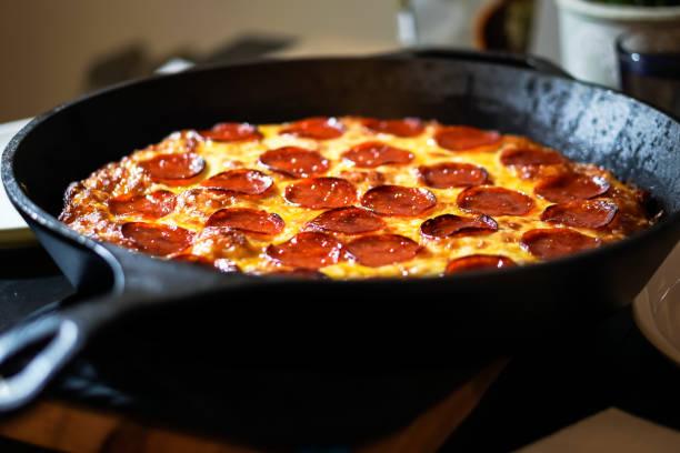 gietijzer deep dish peperoni pizza - dikke pizza close up stockfoto's en -beelden