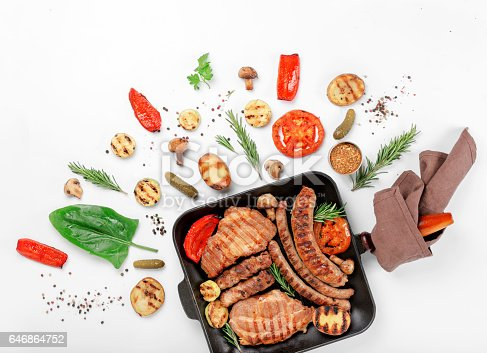 657146780istockphoto Cast iron grill pan with steak and sausages grilled on a white background with grilled vegetables 646864752