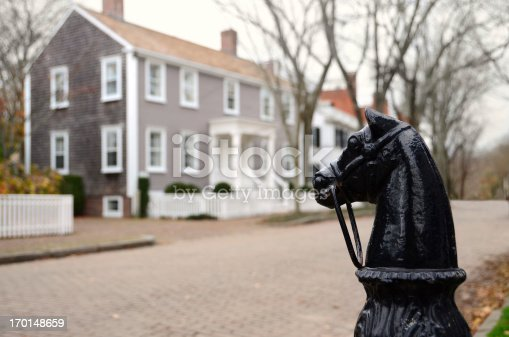 Victorian cast iron hitching post with horse head finial watches over a quiet residential street in Nantucket Town.
