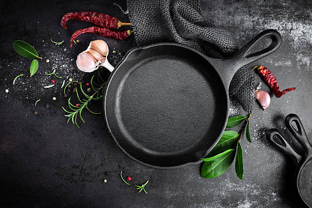 cast iron pan and spices on black metal culinary background stock photo