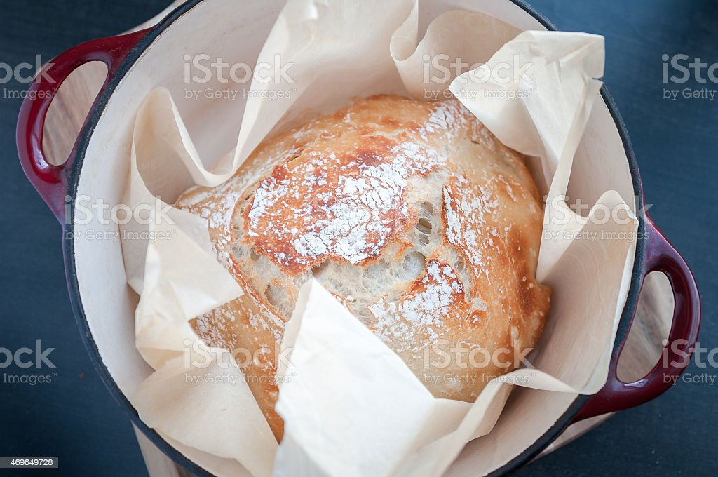Cast iron pot lined in parchment paper with artisan bread stock photo