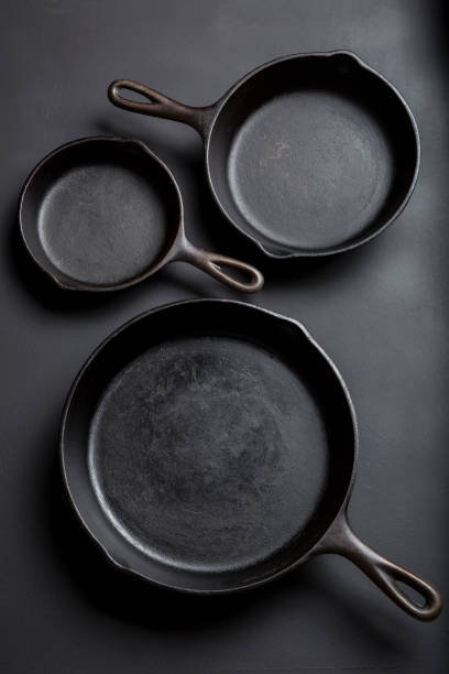 Cast iron skillet collection on black background stock photo