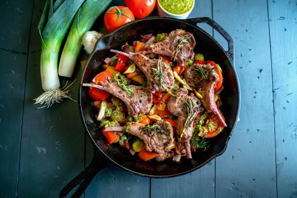 Cast Iron Skillet Filled with Gourmet Lamb Chops and a Vegetable Medley of Brussels Sprouts, Bell Pepper, Garlic, Leeks Tomato, Garlic and Pesto stock photo
