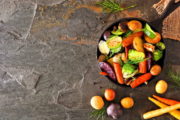 Cast iron skillet of roasted autumn vegetables, above view side border on a dark slate background stock photo