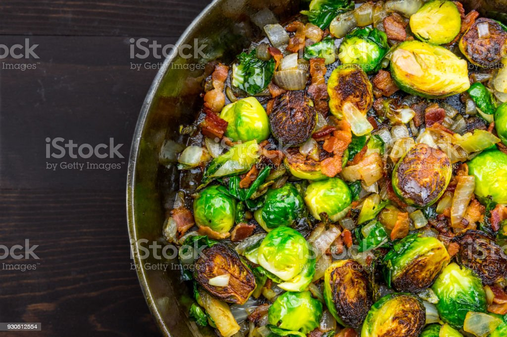 Cast Iron Skillet with Brussels Sprouts with sliver of table stock photo