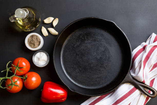 Cast Iron Skillet with copy area on black background with ingredients stock photo