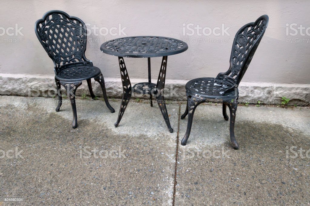 Cast iron table and chairs outside wet floor. stock photo