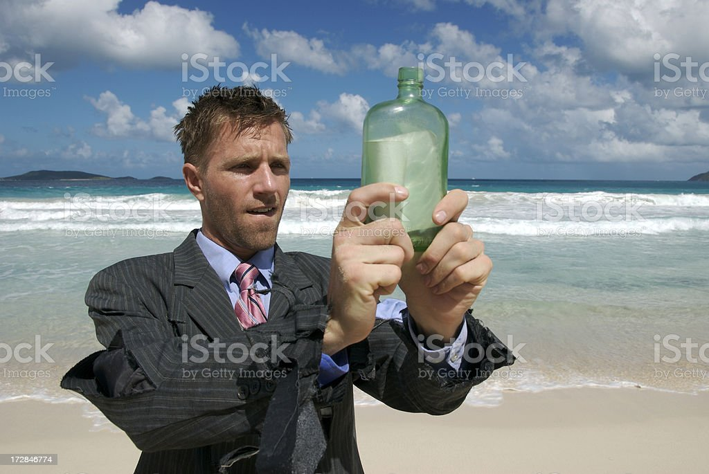 Castaway Businessman Holding Message in a Bottle on Tropical Beach stock photo