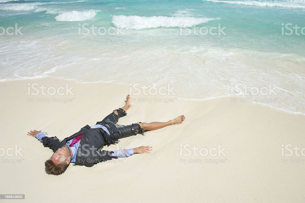 Castaway Businessman Lies Stranded on Tropical Beach royalty-free stock photo