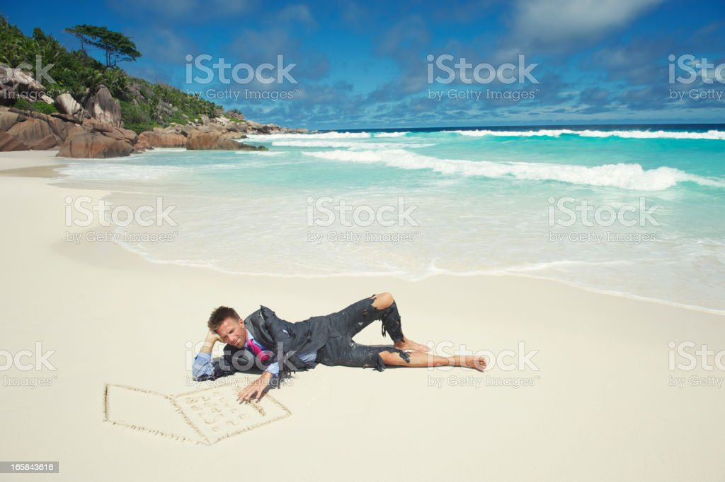 Castaway Businessman Lies Using Laptop in the Sand royalty-free stock photo