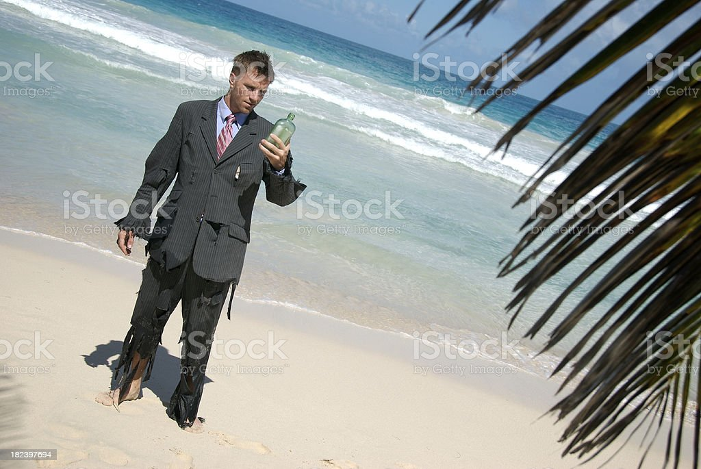 Castaway Businessman Looks at Message in Bottle royalty-free stock photo