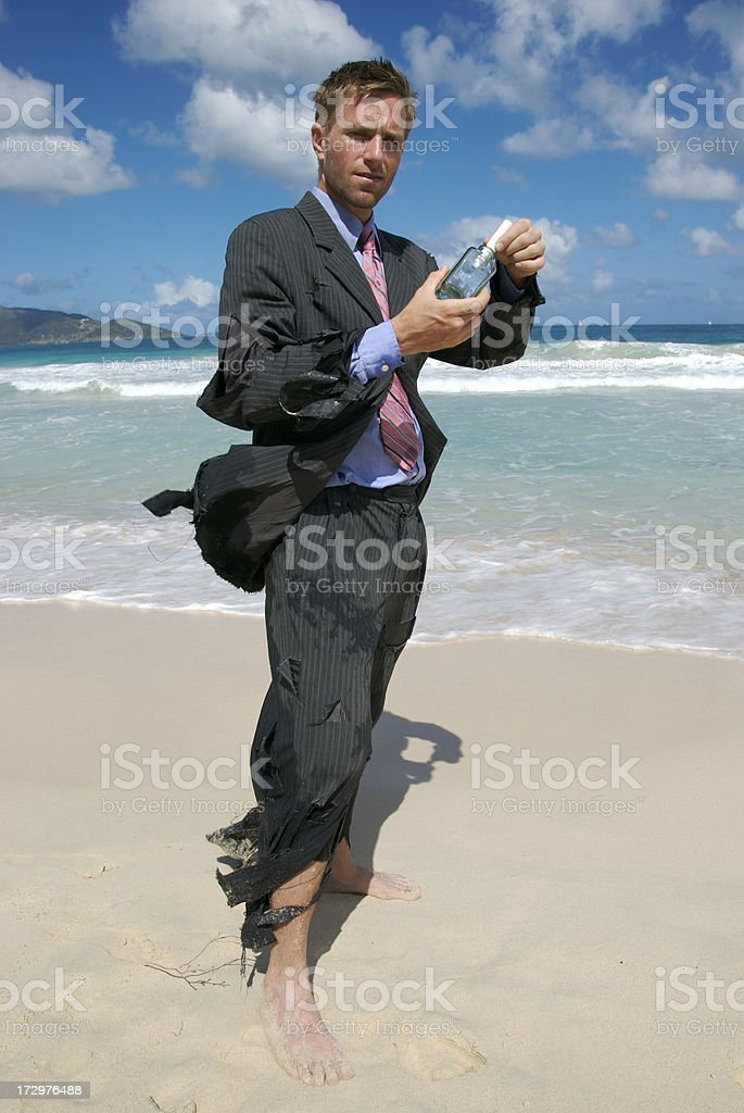 Castaway Businessman Puts Message in a Bottle royalty-free stock photo