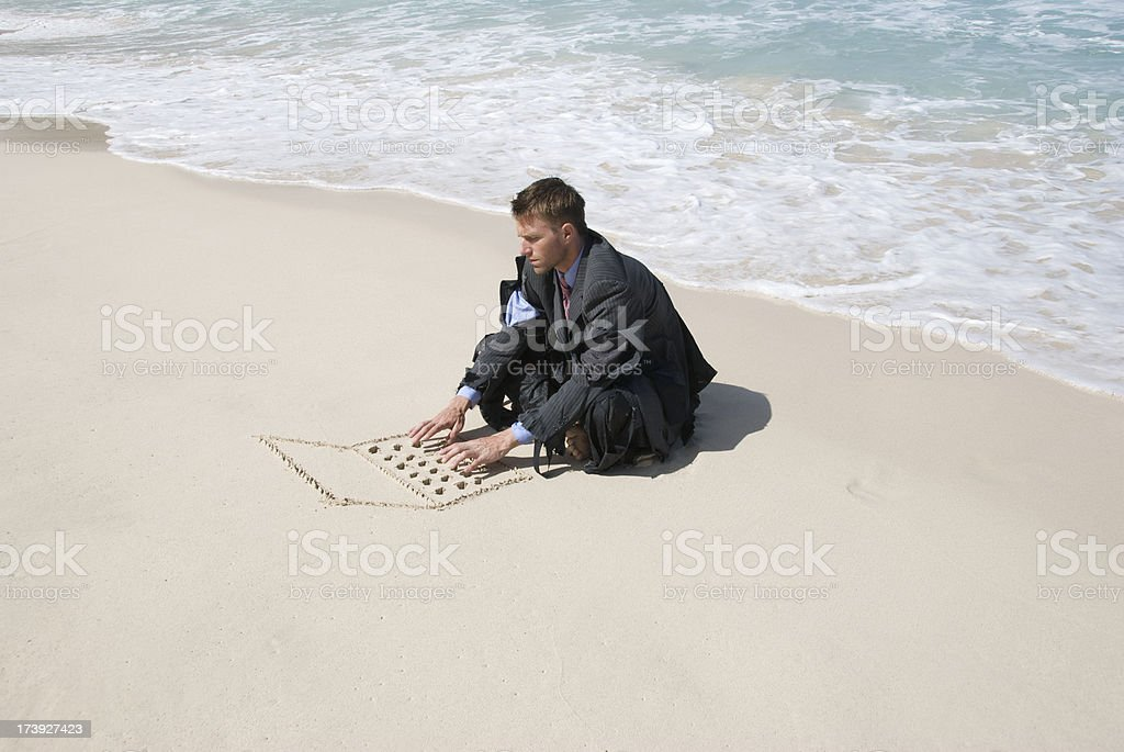 Castaway Businessman Sits and Types on Sand Laptop royalty-free stock photo
