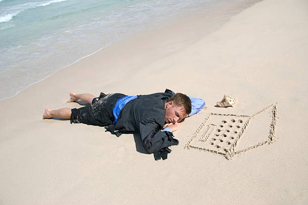 Castaway Businessman Sleeping by his Laptop Computer on the Beach Castaway businessman in a tattered suit sleeping next to his sand computer and shell phone on the beach aground stock pictures, royalty-free photos & images