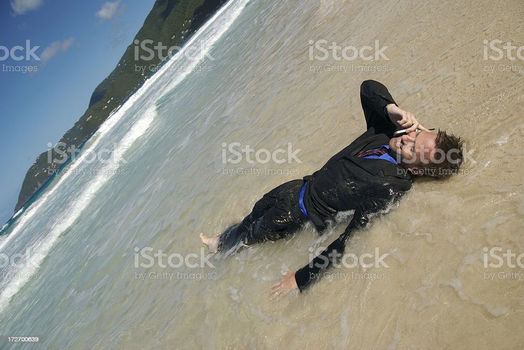 Castaway Businessman Talks on the Phone Floating in Waves royalty-free stock photo